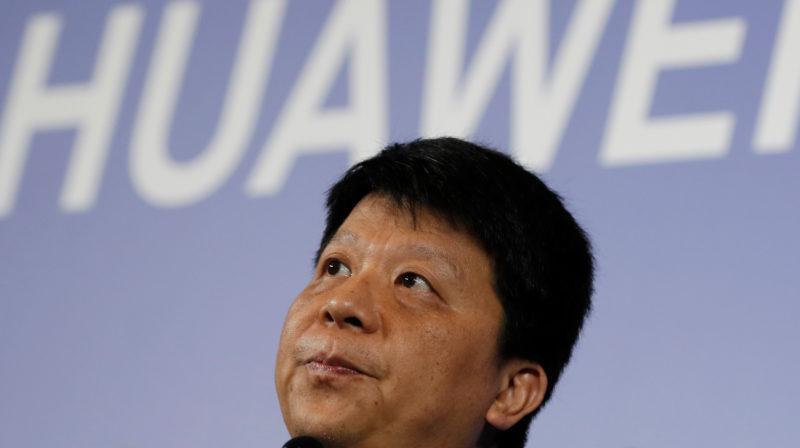 presidente rotativo da Huawei, Guo Ping. Foto em close. Ao fundo, está o logo da Huawei, em branco, sobre uma projeção azul.