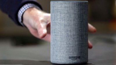Mão pegando alto-falante inteligente Amazon Echo