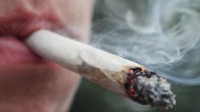 Homem fuma um cigarro de maconha