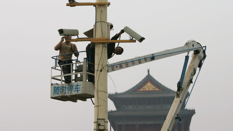 câmera sendo instalada na china. há duas pessoas em um guindaste, onde se vê logogramas chineses. ao fundo, um telhado de um templo oriental.