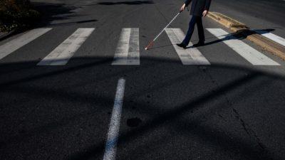 Homem atravessa na faixa de pedestre com bengala para cego