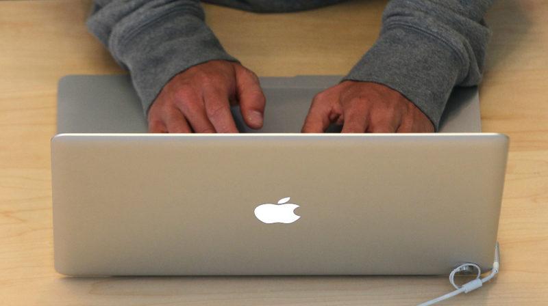 Homem usando laptop da Apple