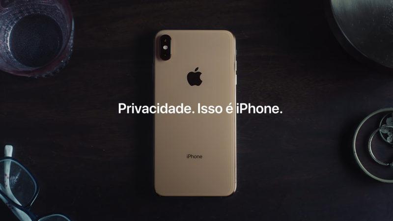 """captura de tela de propaganda de tv do iphone. sobre uma mesa de madeira, está um iphone dourado. ele está virado de frente para a mesa, com as costas viradas para cima. em cima dele, está um grafismo com a frase """"Privacidade. Isso é iPhone."""""""