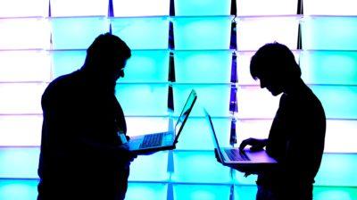 duas pessoas seguram notebooks abertos. elas estão uma de frente para a outra. elas estão em frente a um painel iluminado, de maneira que só suas silhuetas estejam visíveis.