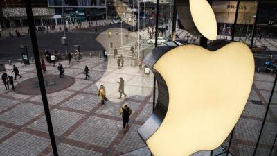 Logo da Apple visto de dentro de uma fachada de vidro.