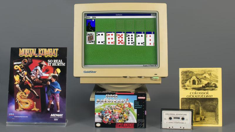 Um monitor de computador com Paciência, caixas de Mortal Kombat e Super Mario Kart, uma fita cassette e um caderno de Colossal Cave Adventure