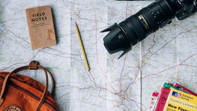 Mapa com um lápis, um caderno, uma câmera, uma bolsa e guias de viagem sobre ele.