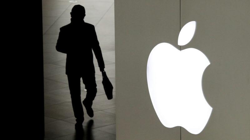 silhueta de um homem saindo por uma porta ao lado de uma parede com o logo da apple
