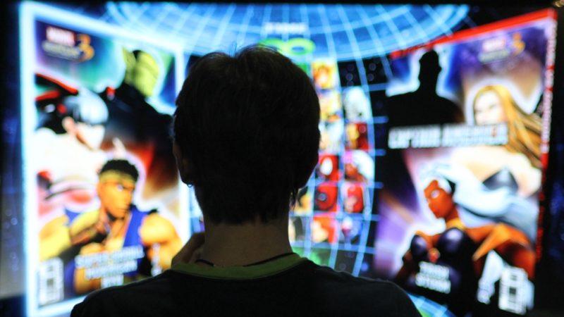 Garoto jogando Street Fighter em uma tela gigante