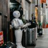 Robô em frente a uma loja ao lado de malas