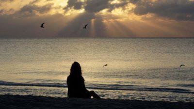 Silhueta de mulher sentada na praia