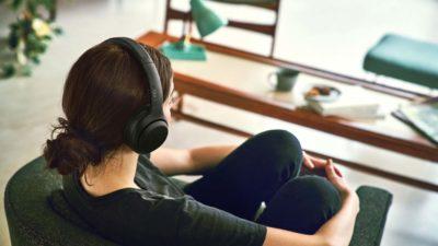 Mulher sentada usando os fones de ouvido Sony XB900N