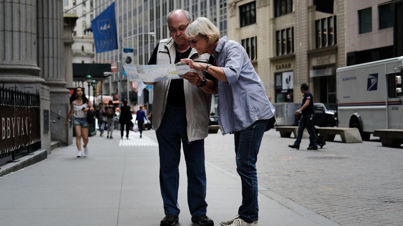 Turistas vendo mapa em uma calçada