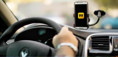 Motorista conduzindo um Renault com o app da 99 aberto no smartphone