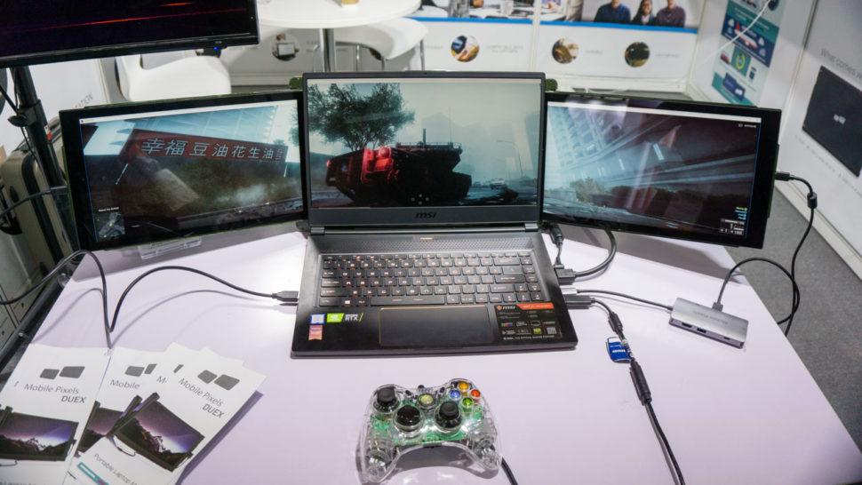 Notebook da MSI com dois monitores extras, cada um preso de um lado do monitor do notebook.