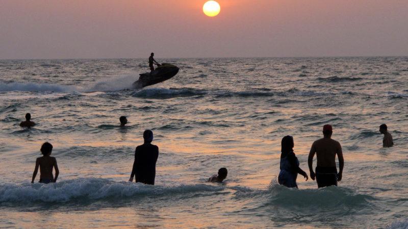 Banhistas na praia durante pôr do Sol