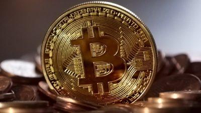 Moeda física com letra B estilizada com símbolo do bitcoin