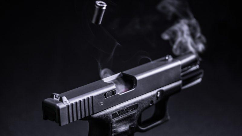 Pistola de cor preta disparando uma bala