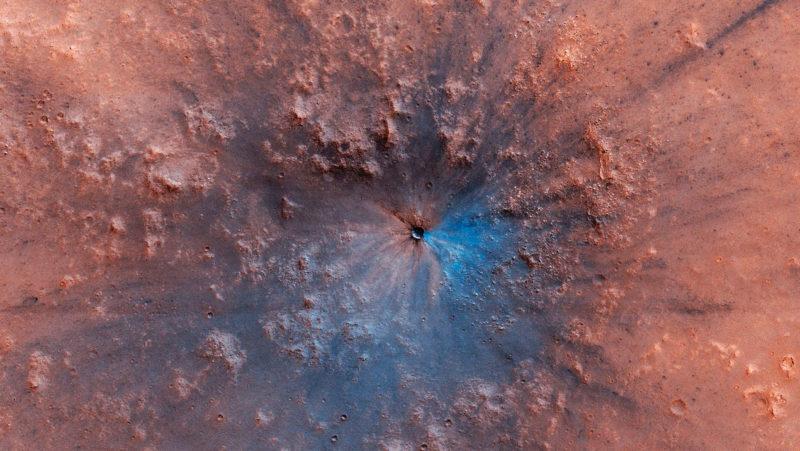 Imagem em falsa cor da nova cratera descoberta em marte. A superfície do planeta é vermelha, há um círculo de relevo acidentado e um buraco no meio, com metade desse buraco pintado de azul. Não é a cor real, é só um indicativo de