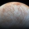 Lua Europa, de Júpiter. Um círculo não enquadrado por inteiro na imagem predominantemente branco com várias linhas avermelhadas em todos os sentidos.
