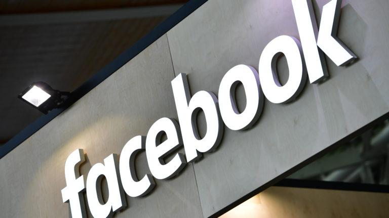 Letreiro do Facebook em uma parede cinza.