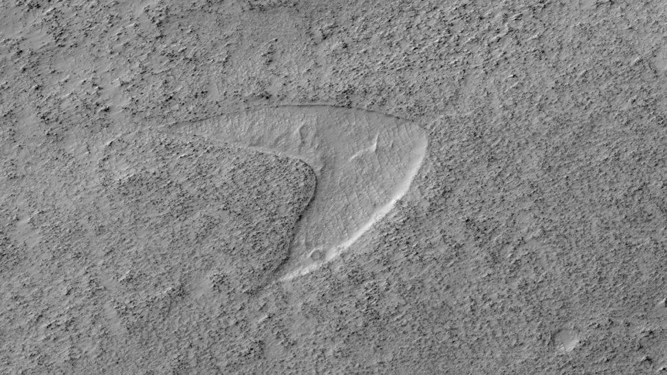 Imagem da superfície com uma letra V afundada no chão. A espessura do V é menor nas pontas e maior na base. A abertura do V está virada para a esquerda.