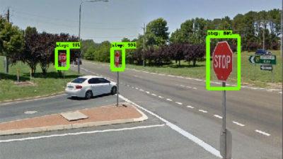 """Imagem mostra uma conversão em duas ruas. Há três placas de """"Pare"""". Todas elas têm retângulos verdes ao redor, desenhados pela inteligência artificial."""