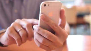 Mão de uma pessoa mexendo em um iPhone 5S