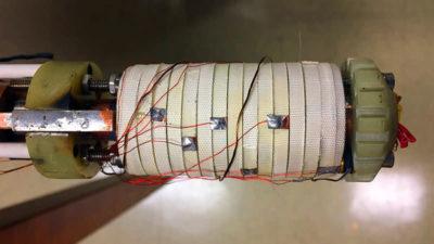 Dispositivo cilíndrico com parafusos na parte de baixo, revestido por faixas brancas no meio e com pequenos fios conectados em toda a sua extensão.