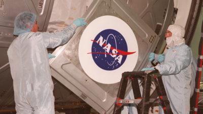 Duas pessoas, usando roupas de proteção, manuseiam uma porta de espaçonave com o logo da NASA.