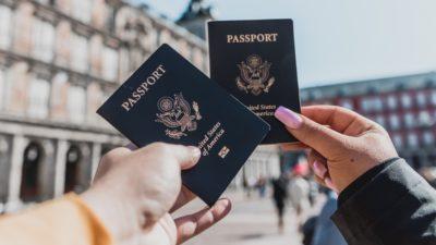 Duas pessoas segurando dois passaportes dos EUA