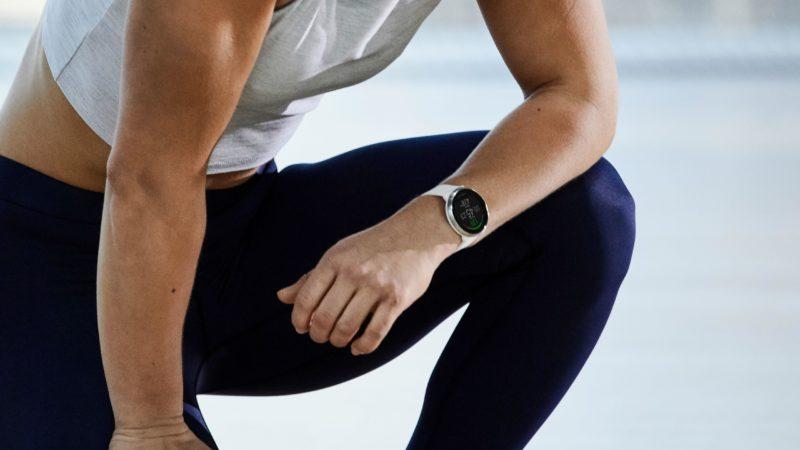 Pessoa de camiseta branca e calça escura agachada com um relógio Polar Ignite no pulso.