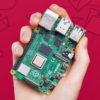 Um Raspberry Pi 4 na mão de uma criança. Ele é uma placa verde, com vários componentes metálicos prateados em suas bordas para conectar outros componentes.