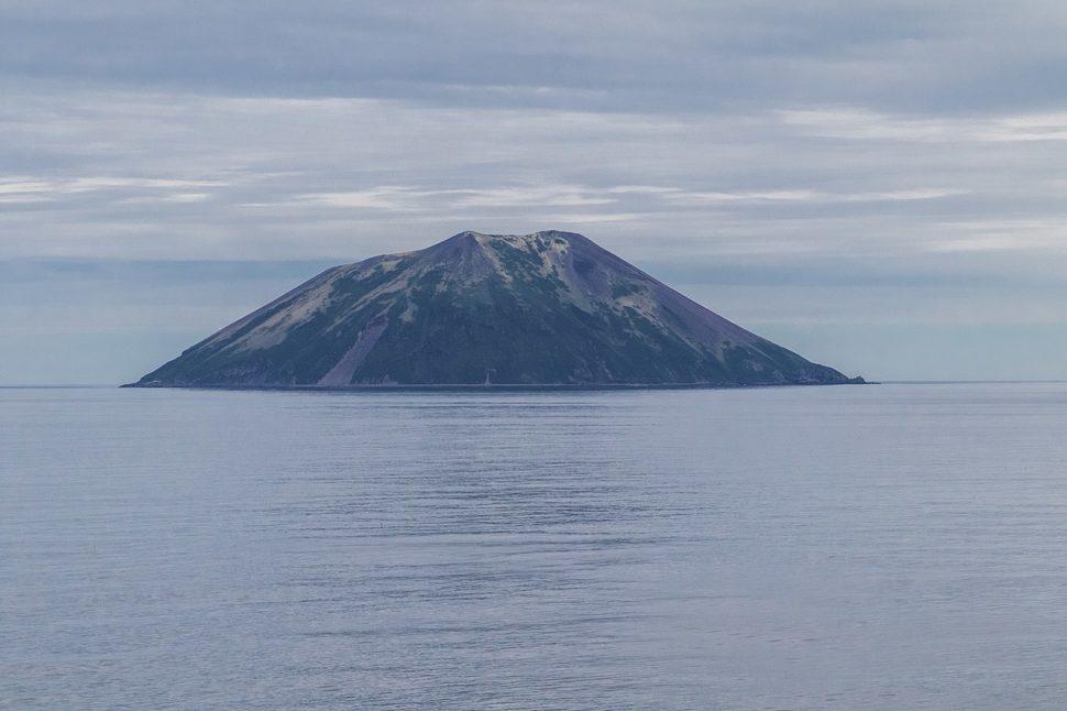 Ilha no mar. A ilha tem um formato próximo de um trapézio e está quase toda coberta por uma vegetação escura.