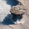 Imagem aérea da erupção do vulcão Raikoke. A metade esquerda é formada por nuvens brancas. No meio da imagem, há a pluma do vulcão se erguendo sobre as nuvens. Ela é mais escura, em um tom entre o cinza e o marrom. Na metade direita da imagem, há nuvens mais escuras, acinzentadas.