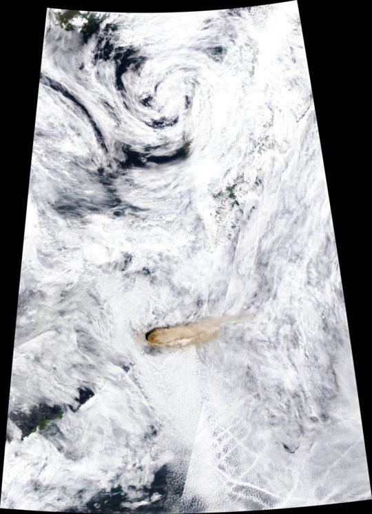 Imagem de satélite formada quase que inteiramente por nuvens brancas, com algumas falhas mostrando o azul escuro do mar por baixo delas. Pouco abaixo da metade da imagem, há um ponto em bege escuro, com nuvens em bege se espalhando para a direita.