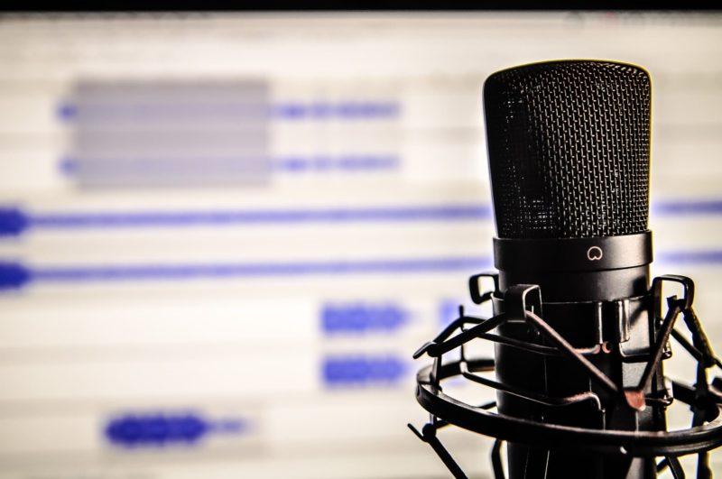 Microfone com tela ao fundo com edição de áudio