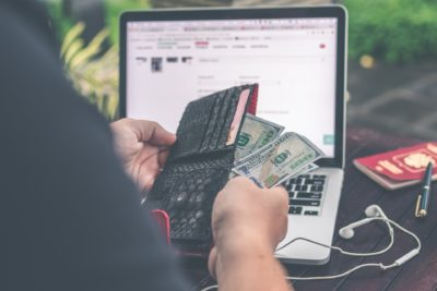 Pessoa segurando carteira com dinheiro em frente a um laptop