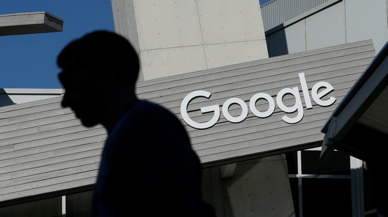 Homem passa em frente à logotipo do Google na sede da empresa na Califórnia, EUA