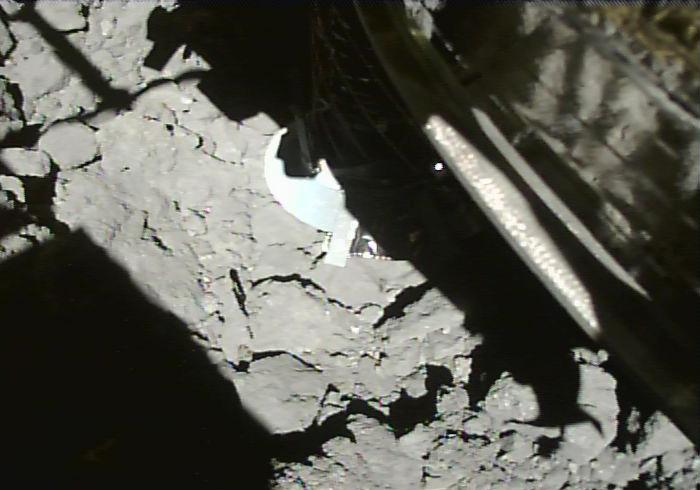 Imagem preto e branco mostra uma estrutura mecânica pousando em um chão rochoso