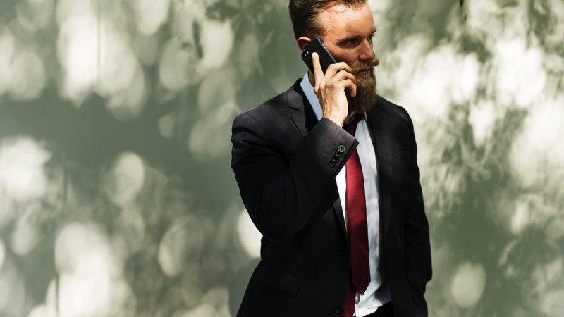 Homem vestido de terno faz ligação pelo celular