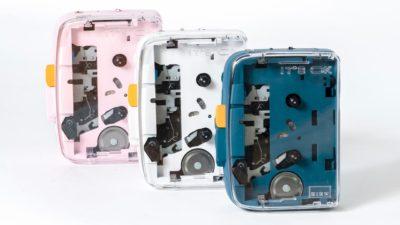 Três toca-fitas IT'S OK. Um é rosa claro, outro é branco e outro é azul escuro. A tampa do compartimento de fitas é transparente e deixa a mostra parte da mecânica dos aparelhos.