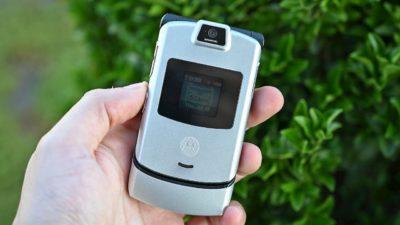 Motorola V3 clássico na cor prata sendo segurado por uma mão esquerda. O aparelho é menor que um smartphone atual, tem uma tela secundária no meio da tampa e uma câmera na parte superior.