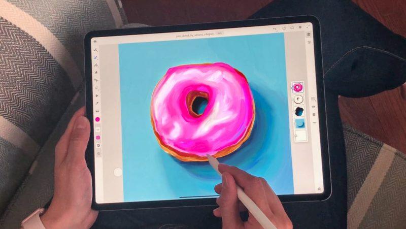 Foto de uma pessoa usando o Adobe Fresco em um iPad. Há um donut cor de rosa na tela. A pessoa está segurando um Apple Pencil. Na parte de esquerda da tela, há uma coluna de ferramentas. Na parte direito, camadas com as diferentes cores usadas no donut e no fundo.