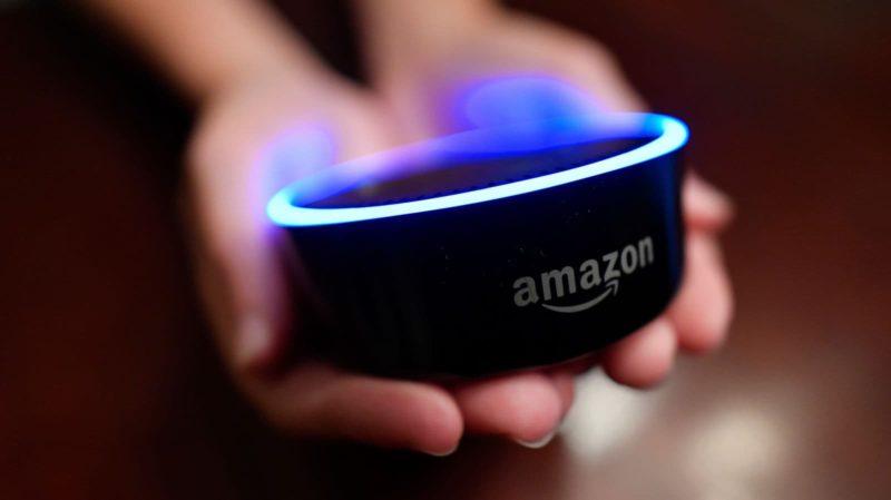 Pessoa segura um Amazon Echo, alto-falante com assistente Alexa, da Amazon