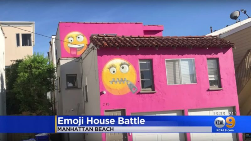 Casa com a fachada pintada de rosa e dois emojis desenhados