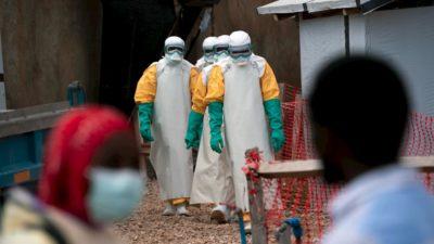 Trabalhadores da saúde começando o expediente em uma zona de epidemia de ebola em Beni, República Democrática do Congo, em julho de 2019. Há quatro pessoas vestidas com máscaras, luvas verdes, mangas amarelas e aventais e botas brancas, no centro da imagem. O chão é de terra. No primeiro plano, mas desfocado, há uma mulher negra com máscara cirúrgica e um homem negro.