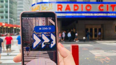 Celular com o Google Maps Live View aberto. Função de realidade aumentada mostra seta com direção para caminhadas.