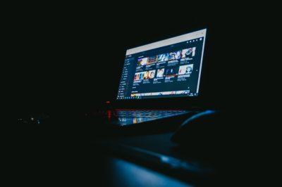 Laptop com YouTube na tela em uma sala escura
