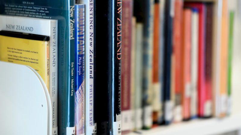 Livros em uma estante. Os livros em destaque são guias de viagem para a Nova Zelândia e estão em inglês.